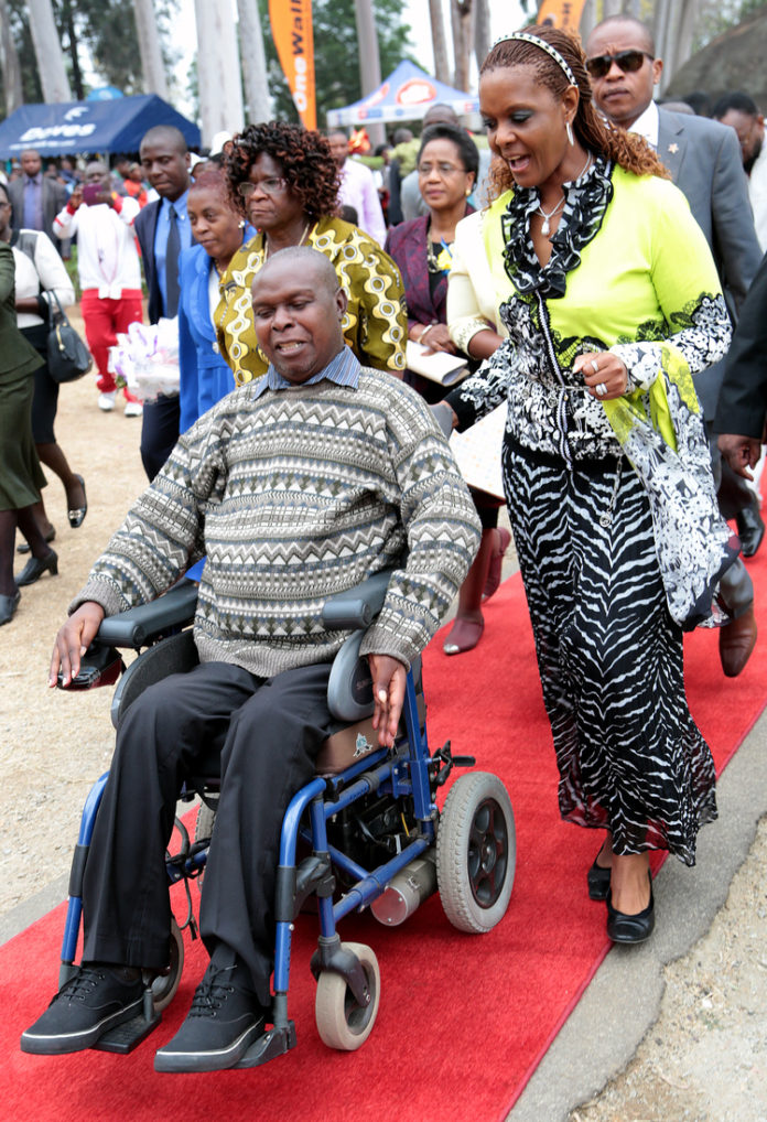 First Lady Dr Grace Mugabe assists Deputy Director of Danhiko Project Mr Godfrey Majonga during Danhiko Paralympic Games
