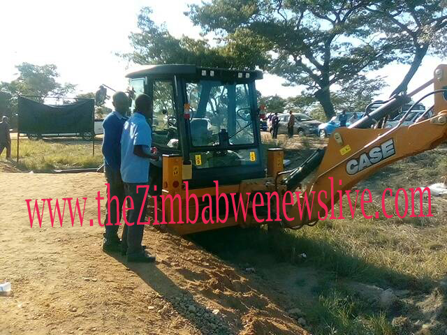 The half-buried front-end loader with a backhoe that was partially buried to make it easier for Mugabe to get into its cockpit.