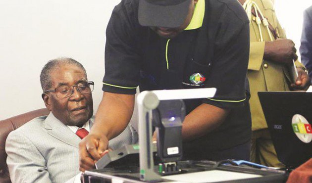 President Mugabe is taken through the inaugural biometric voter registration (BVR) process by Zimbabwe Electoral Commission computer technician Noel Shumba at State House in Harare yesterday, marking the commencement of voter registration ahead of the 2018 harmonised elections. — (Picture by Chief Photographer Believe Nyakudjara)