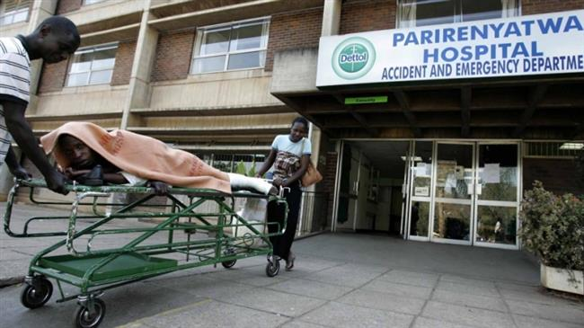 The file photo shows a patient being taken home on a stretcher by his relatives from a hospital in Harare, Zimbabwe. (Photo by Reuters)