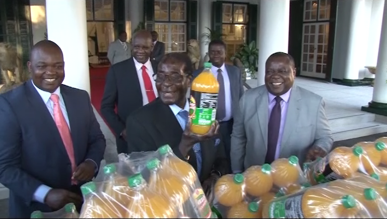 President Mugabe receives a donation of 100 cases of Mazoe Orange Crush from Mr Charles Msipa