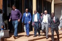 Trial ... Psychology Maziwisa (in blue suit) and Oscar Pambuka (far right) leave court with their lawyer Jonathan Samukange (centre)