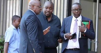 Wicknell Chivhayo chats to his lawyers Advocate Lewis Uriri (right) and Mr Wilson Manase at the court yesterday