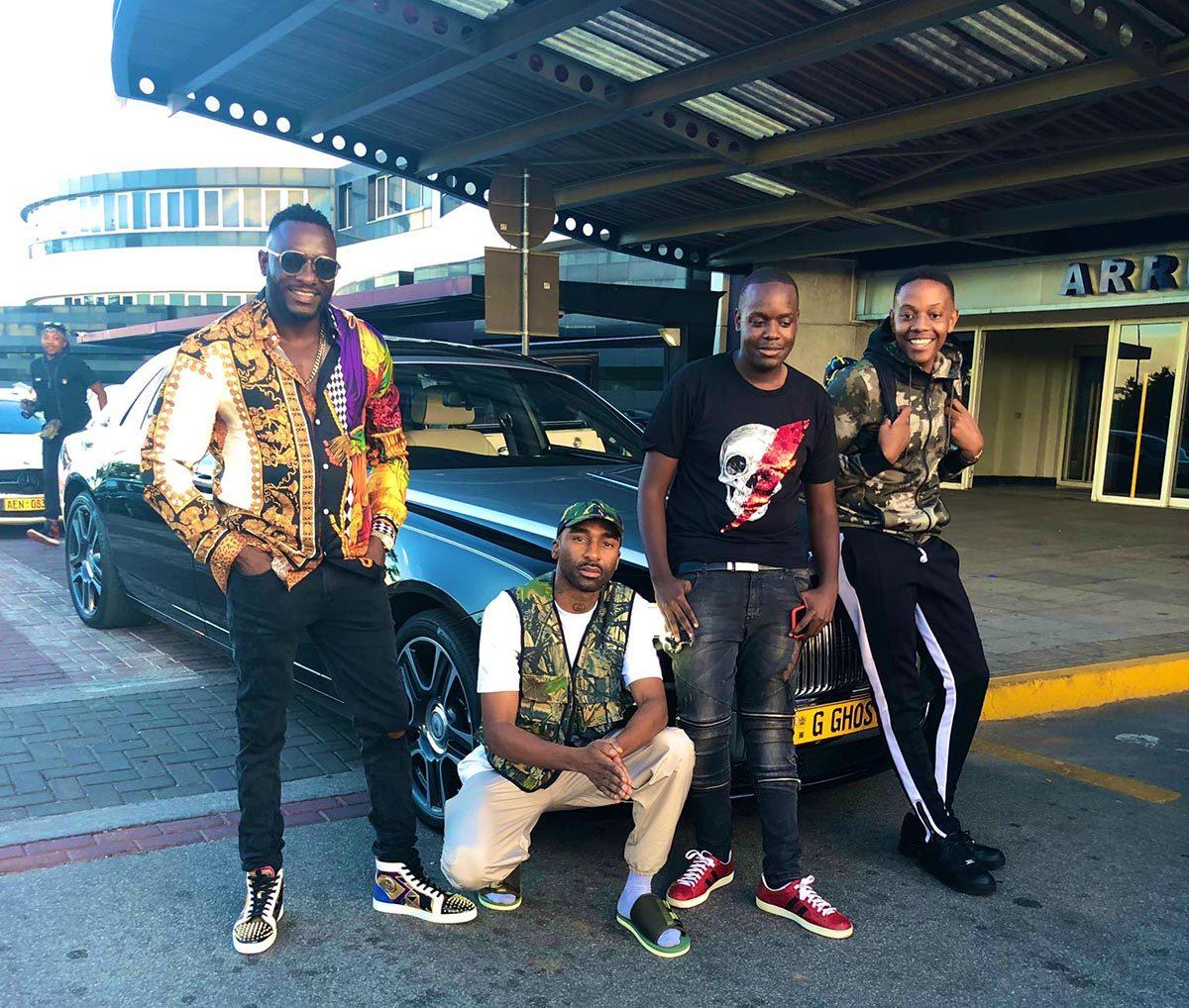Risking all ... Riky Rick (crouching) and Chatunga (far right) wear camouflage at the Robert Gabriel Mugabe International Airport (Picture: Riky Rick/Twitter)