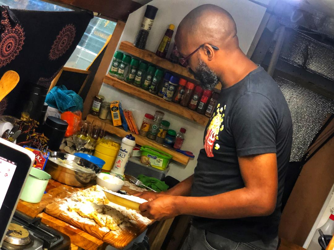 Carl Joshua Ncube in the kitchen cooking Sour Milk Chicken