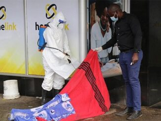 The picture shows Bulawayo City Council employees spraying the body with a disinfectant ahead of collection by the police.
